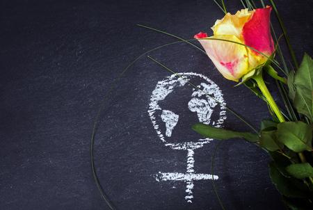 Rose en een krijt getrokken vrouwelijke teken met aarde wereldbol op een schoolbord, concept van de dag van de vrouw, de rechten en feminisme van de vrouw, kopieer ruimte
