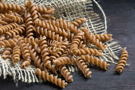 wholemeal pasta fusilli from organic whole grain spelt on burlap and dark rustic wood, close up shot