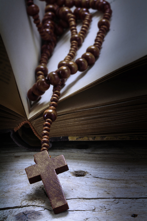 christian faith: catholic wooden rosary beads with cross in an old book on rustic vintage wood, religious symbol concept, toned with color filter, selected focus, narrow depth of field, vertical Stock Photo