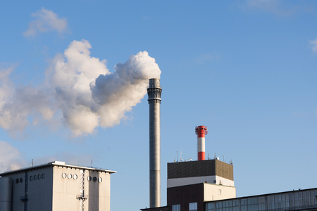 ozone layer: Industrial chimney with smoke and factory buildings against the blue sky with copy space