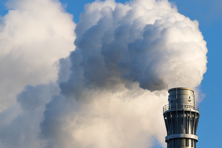 ozone layer: thick industrial smoke from a factory chimney, blue sky, copy space Stock Photo