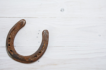 lucky: lucky horseshoe, used and with rust, on white painted wood, symbol for good luck, background with copy space