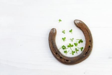 herradura: herradura vieja suerte con un par de peque�as hojas de tr�bol, sobre madera blanca, s�mbolo de buena suerte, de fondo con espacio de la copia Foto de archivo