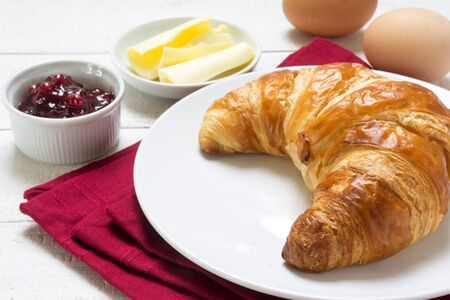 Sunday breakfast with croissant, jam and eggs, red napkin on a white wooden table, selected focus, narrow depth of field