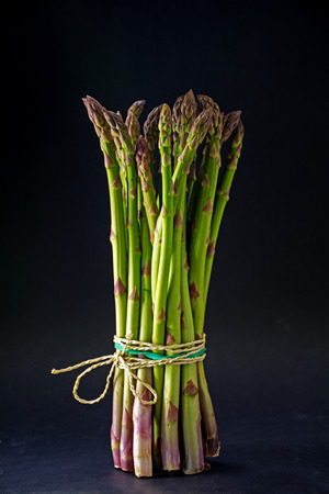 narrow depth of field: bunch green asparagus standing on a dark background, selected focus and narrow depth of field