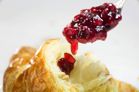 breackfast: red cranberry jam on a spoon dripping on a fresh croissant, breackfast closeup shot with selected focus and narrow depth of field