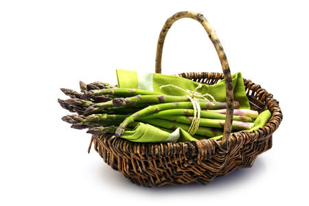 harvest basket: green asparagus in a harvest basket, isolated with small shadow on a white background, selected focus