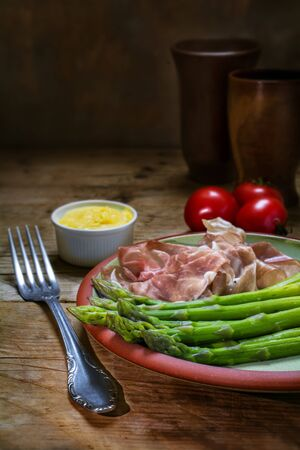narrow depth of field: green asparagus with gammon and hollandaise sauce on an earthenware plate on a rustic wooden table, dark background, copy space, vertical,  selected focus, narrow depth of field