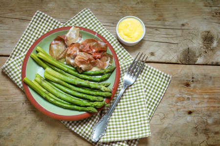 air dried: green asparagus with gammon and dip on an earthenware plate on a napkin, rustic wooden background, view from above, copy space Stock Photo