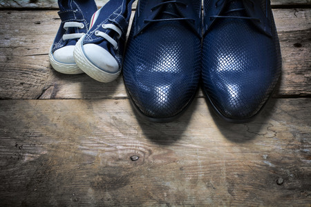 father's business shoes and kids sneakers side by side on rustic wood, concept of family, single parent and father's day, view from above
