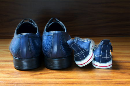 Men shoes and children sneakers from behind side by side on the wooden floor, concept of family, at home and fathers day