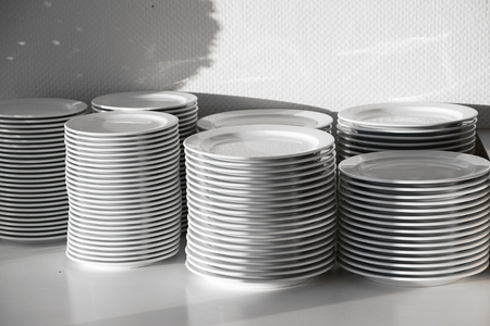 narrow depth of field: several stacks of white porcelain plates, selected focus narrow depth of field