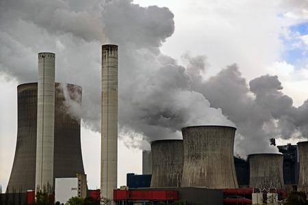 energiecentrale met schoorstenen en dampende koeltorens, grijze wolken stijgen in de hemel, concept voor energie-industrie, CO2-uitstoot en bescherming van het milieu