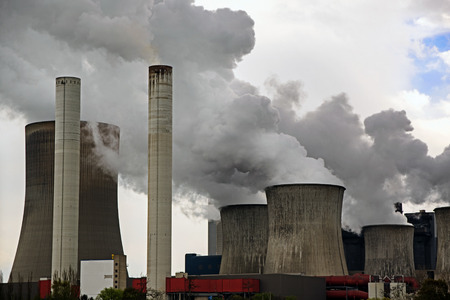 power plant with chimneys and steaming cooling towers, gray clouds rise in the sky, concept for energy industry, co2 emissions and environmental protection
