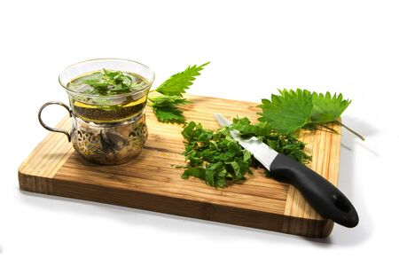 detoxing: Preparing nettle tea, leaves, knife and teacup on a wooden cutting board isolated with shadows on a white background, selected focus, narrow depth of field
