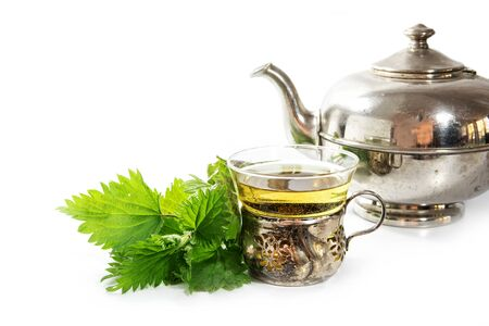 narrow depth of field: silver teapot and vintage cup with nettle tea and some fresh leaves on a white background, healing herb directly from nature, selected focus, narrow depth of field