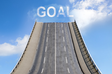 next year: Road leads upwards in the blue sky with white clouds, text GOAL, business concept for new goals, future and success