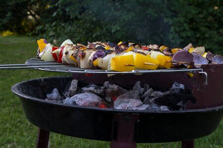 small old barbecue grill with glowing charcoal and shashlik skewes in the garden, selected focus and narrow depth of field