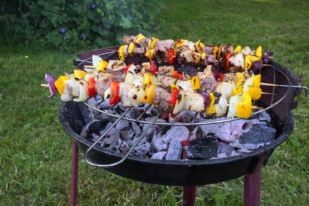 shashlik skewers with onions, peppers and meat on a small old barbecue grill in the garden, selected focus and very narrow depth of field