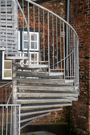 Modern Exterior Spiral Staircase Of Metal In The Backyard On An Old Brick  Building, Fire