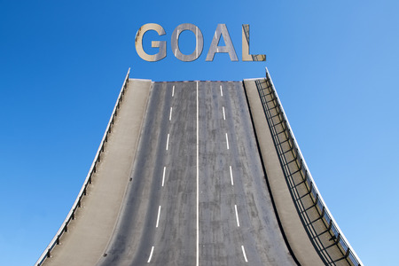 Road leads directly upwards in the blue sky with text GOAL, business concept for new goals, future and success