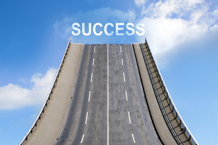 Road leads upwards in the blue sky with white clouds, text SUCCESS,  business concept for future and new goals