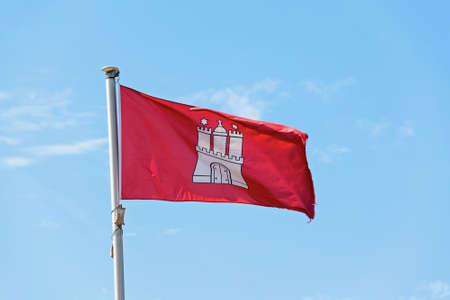 city coat of arms: Flag of the City of Hamburg, Germany, fluttering in the wind against the blue sky and shows the coat of arms white castle on a red background, copy space Stock Photo
