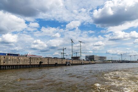 panoramic view on a port with cranes and construction sites, cloudy blue sky and brown water, concept of economic upturn or unfinished buildings, copy space Stock Photo