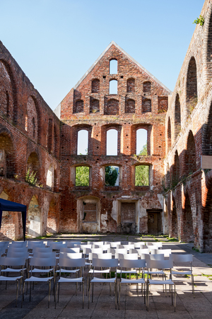 seating area: inside a brick ruin of a medieval monastery without roof with seating arrangements for an open air event, concert and theater, Bad Doberan, northern Germany, vertical