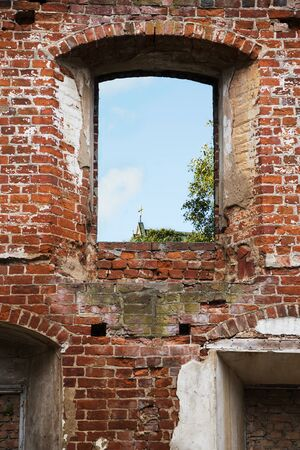 refurbish: empty window in an old brick wall of a monastery ruin with a view to the small cross of a church, Bad Doberan, northern Germany, copy space
