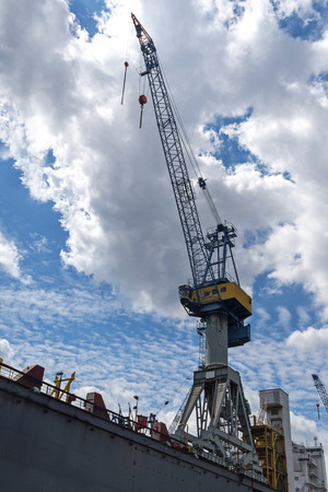 Cargo crane against the blue sky with clouds in the port of Hamburg, Germany, vertical low angle shot, copy space Stock Photo