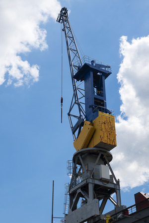 Cargo crane against the blue sky with clouds in the port of Hamburg, Germany, vertical, copy space