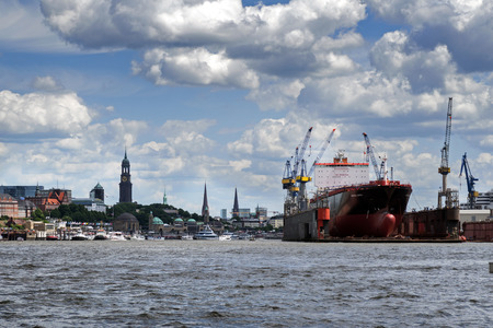 drydock: Hamburg, Germany - June 11, 2016: City of Hamburg and the container ship Montreal Express in a dry dock, view from the cargo port in the river Elbe, typical cloudy sky, copy space Editorial