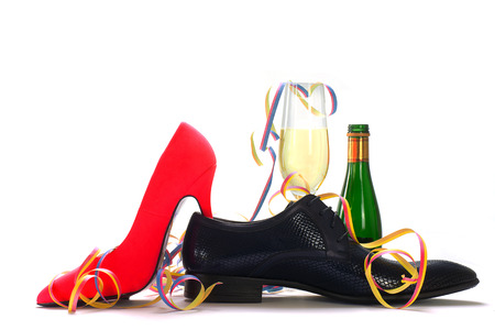 love affair: ladies red high heels and black mens shoes with champagne and streamers, concept for gender topics such as party, dating, flirting, love affair, isolated with shadows on a white background Stock Photo