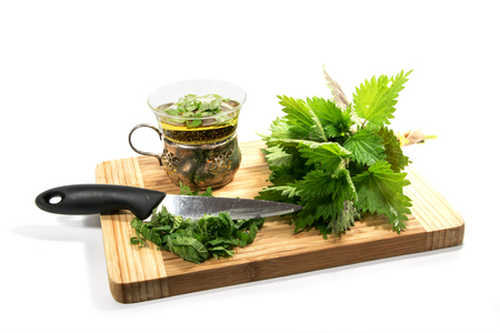 bunch of fresh nettle, kitchen knife, sliced leaves and a cup with nettle tea on a cutting board, isolated with shadows on a white background, selected focus, narrow depth of field