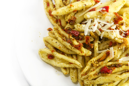 olio: homemade pasta variety called capunti with aglio e olio, which is garlic and oil, thereto pickled tomatoes and  parmesan cheese, specialty from southern Italy,  closeup with view from above, background fades to white