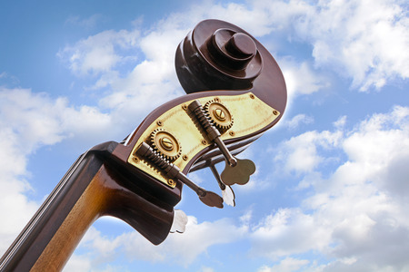 double bass, detail of the music instrument  neck, head with tuning pegs and scroll against a blue sky with clouds, view from below, copy space Stock Photo