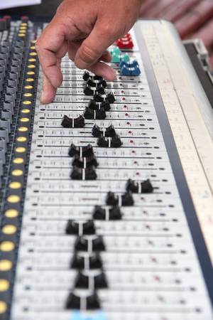 signal device: Part of a professional sound mixing console, hand controls the slider, music device for audio signal Stock Photo