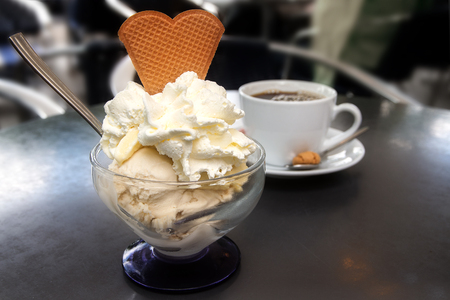 shady: sundae with ice cream, whipped cream and biscuit in heart shape and a cup of coffee on a metal table in a shady street cafe Stock Photo