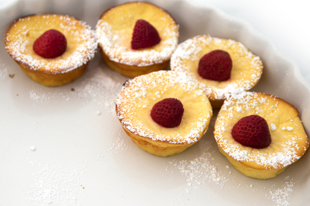 narrow depth of field: Small strawberry  muffin tarts on a half-empty plate on a summer party, copy space, closeup with selected focus and narrow depth of field