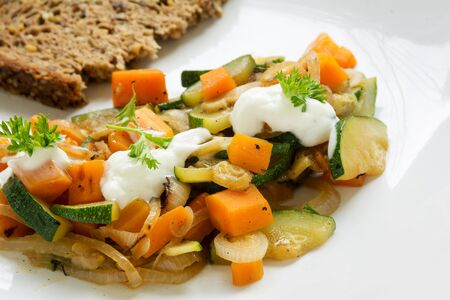 summer vegetables from zucchini and carrots with soured cream and parsley garnish, plus a slice of whole grain bread, a light and healthy dish on a white plate, closeup with selected focus and narrow depth of field Stock Photo
