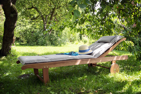 daybed: garden daybed made of wood with hat and sunglasses on a sunny meadow in the orchard, enjoy leisure in nature Stock Photo
