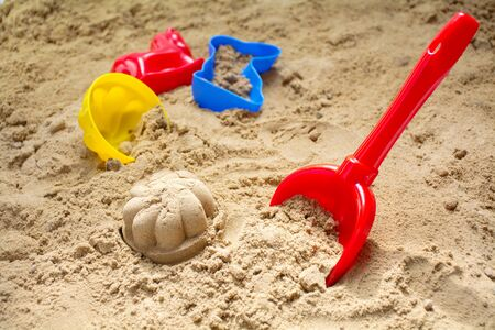 red toy shovel and colorful plastic molds in a sandbox or at the beach, concept for family summer holidays at sea,  selected focus, narrow depth of field