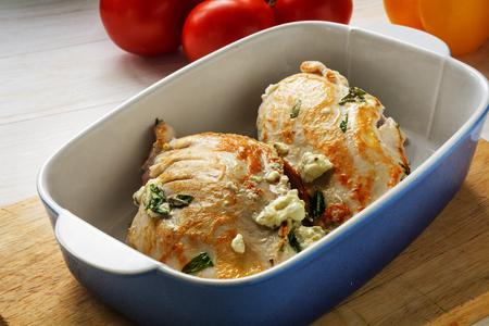 gefrituurde gevulde kipfilet in mediterrane stijl met feta-kaas en kruiden in een ovenschaal op een houten keukenbord, geselecteerde focus en smalle scherptediepte
