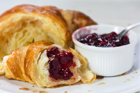 fresh croissant with red cranberry jam for breakfast, closeup with selected focus and narrow depth of field