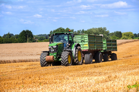 john deere: KALKHORST, GERMANY, AUGUST 16, 2016: John Deere tractor with two trailers working on the golden field in a rural landscape against the blue sky, northern Germany Editorial