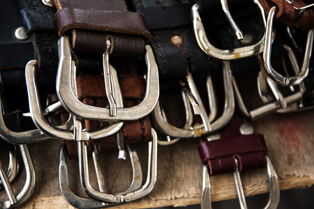buckles: several silver buckles of leather belts for sale at a flea market, selected focus,  narrow depth of field Stock Photo