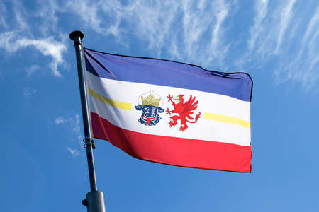 grasping: flag of Mecklenburg-Vorpommern blowing in the wind against the blue sky, a symbol of the federated state on the Baltic Sea in northeastern Germany with the bulls head for Mecklenburg and the grasping of Vorpommern Stock Photo