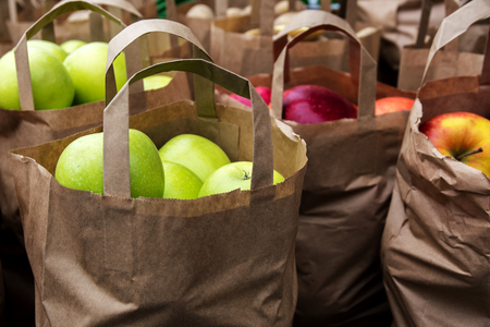 paper bags with organic green and red apples on the market, fresh harvest from the farm, selected focus on the anterior bag, very narrow depth of field