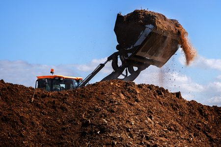 Excavator shovel working on a large heap of manure, organic fertilizer for the field, blue sky, copy space Stockfoto